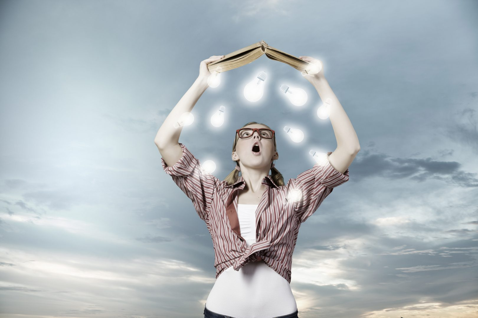 girl holding book above head with lightbulbs around