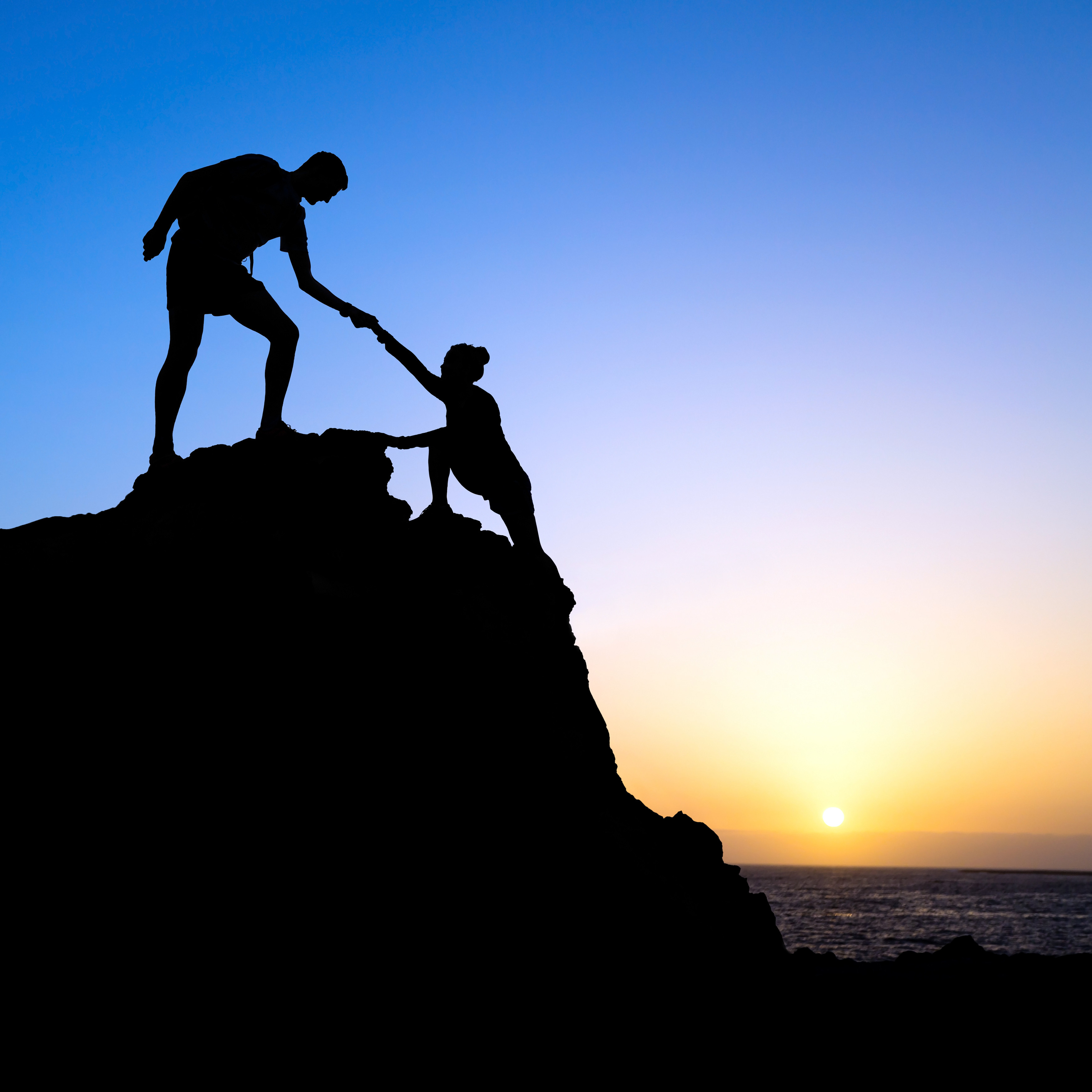 person helping another person on top of hill