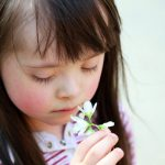 down syndrome girl looking at flower closeup