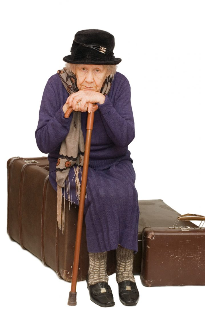 elderly woman sitting on suitcase waiting