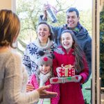 family at door with presents Christmastime