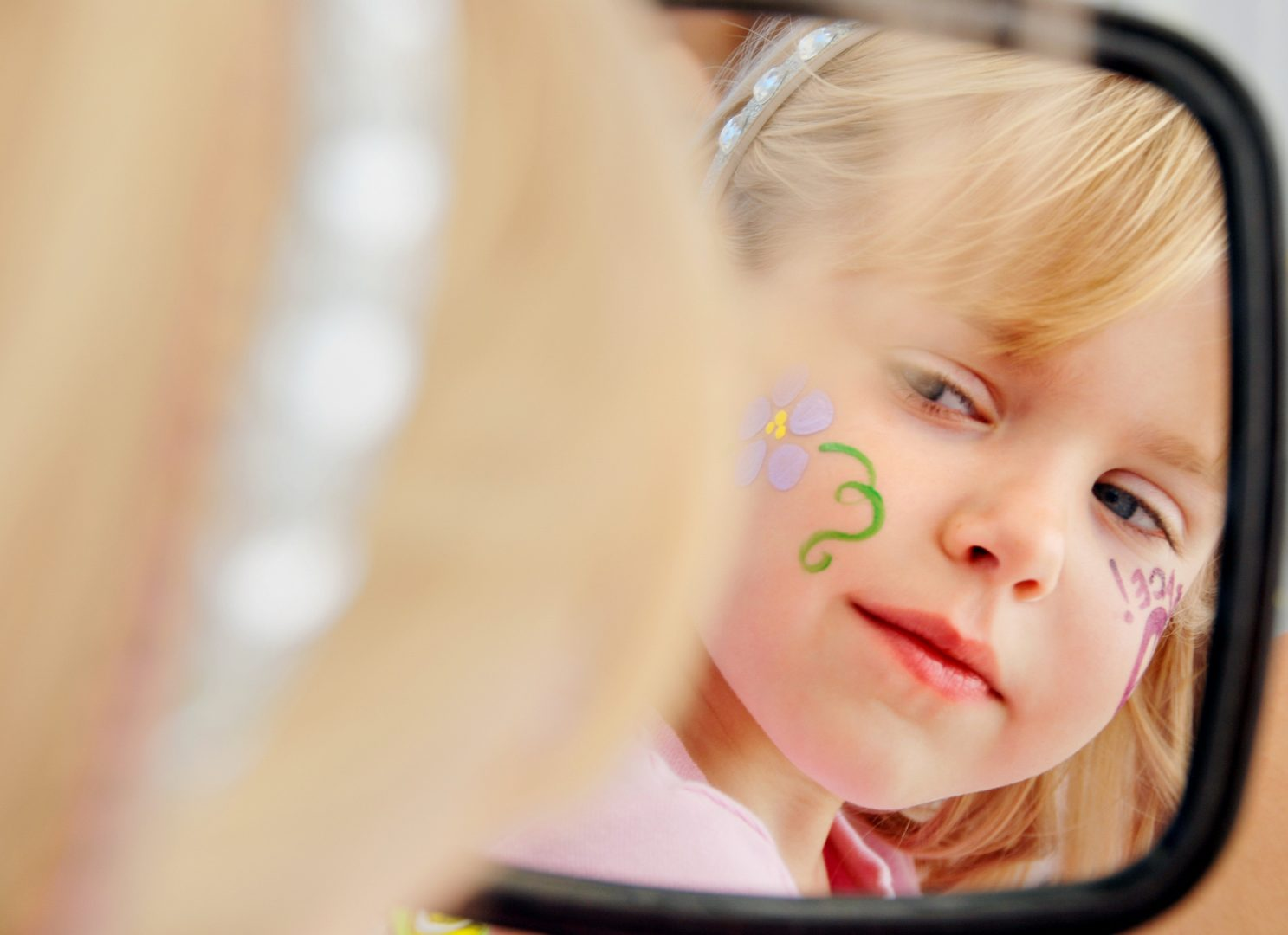 girl looking in mirror face painting on cheek