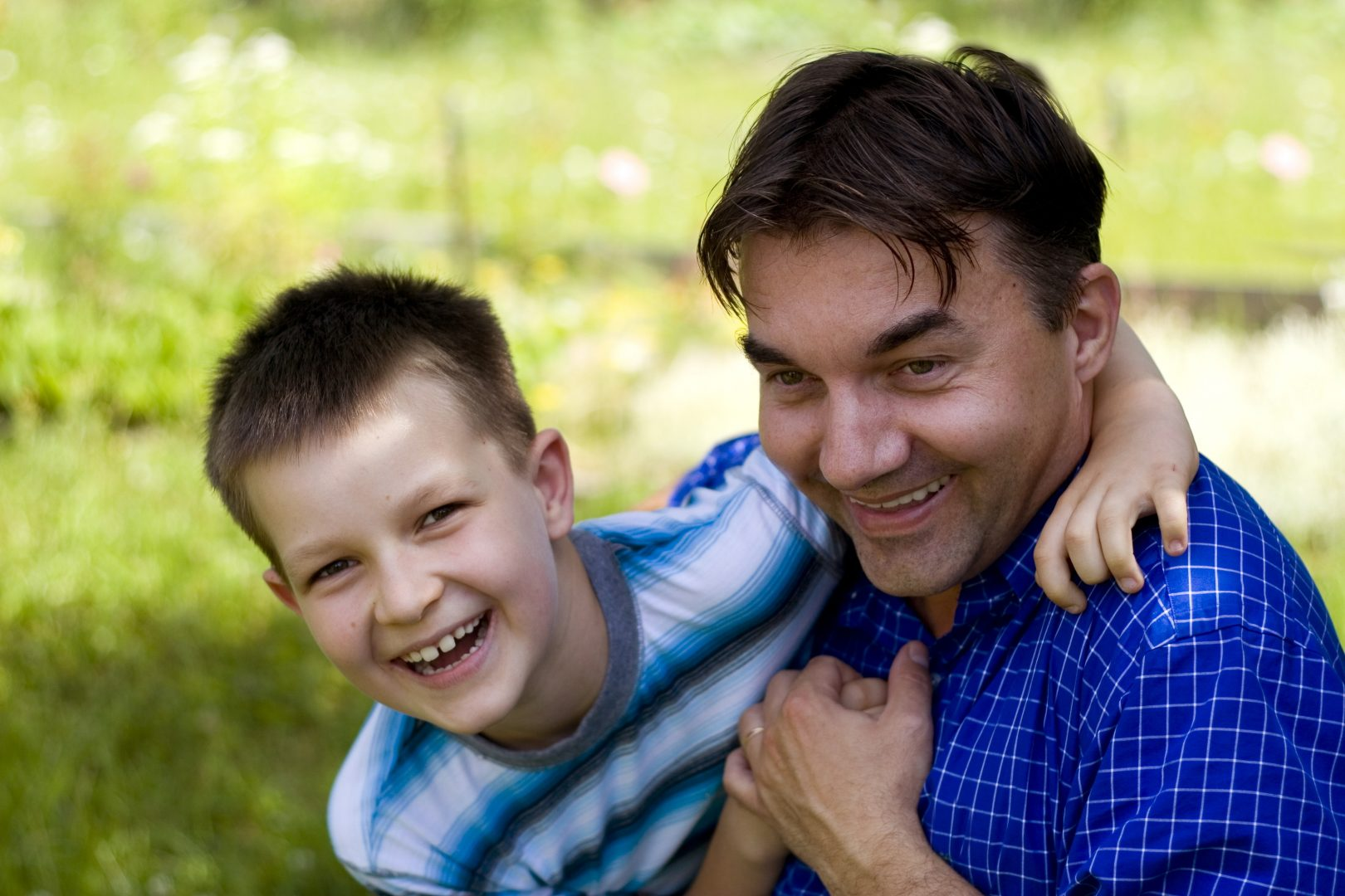 boy hugging father playing outside