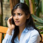 woman talking on smart phone sitting on park bench