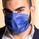 face of young man wearing blue surgical mask facing camera