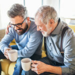 An adult hipster son and senior father sitting on sofa indoors at home, talking with coffee mug in hand