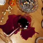 wine glass tipped over with spilled wine surrounded by pills and full ashtray