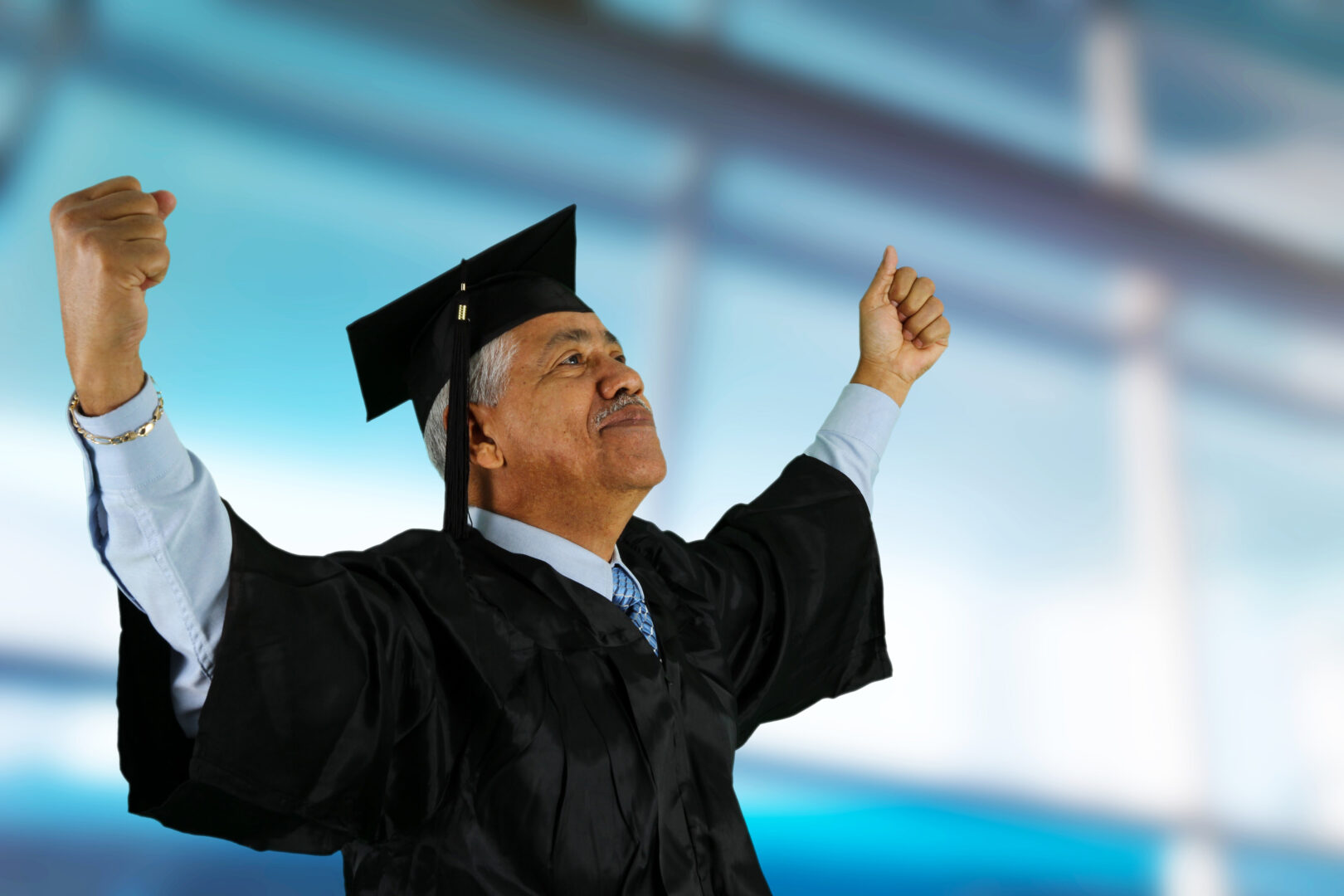 senior man in graduation robe shouting for joy with arms up in air