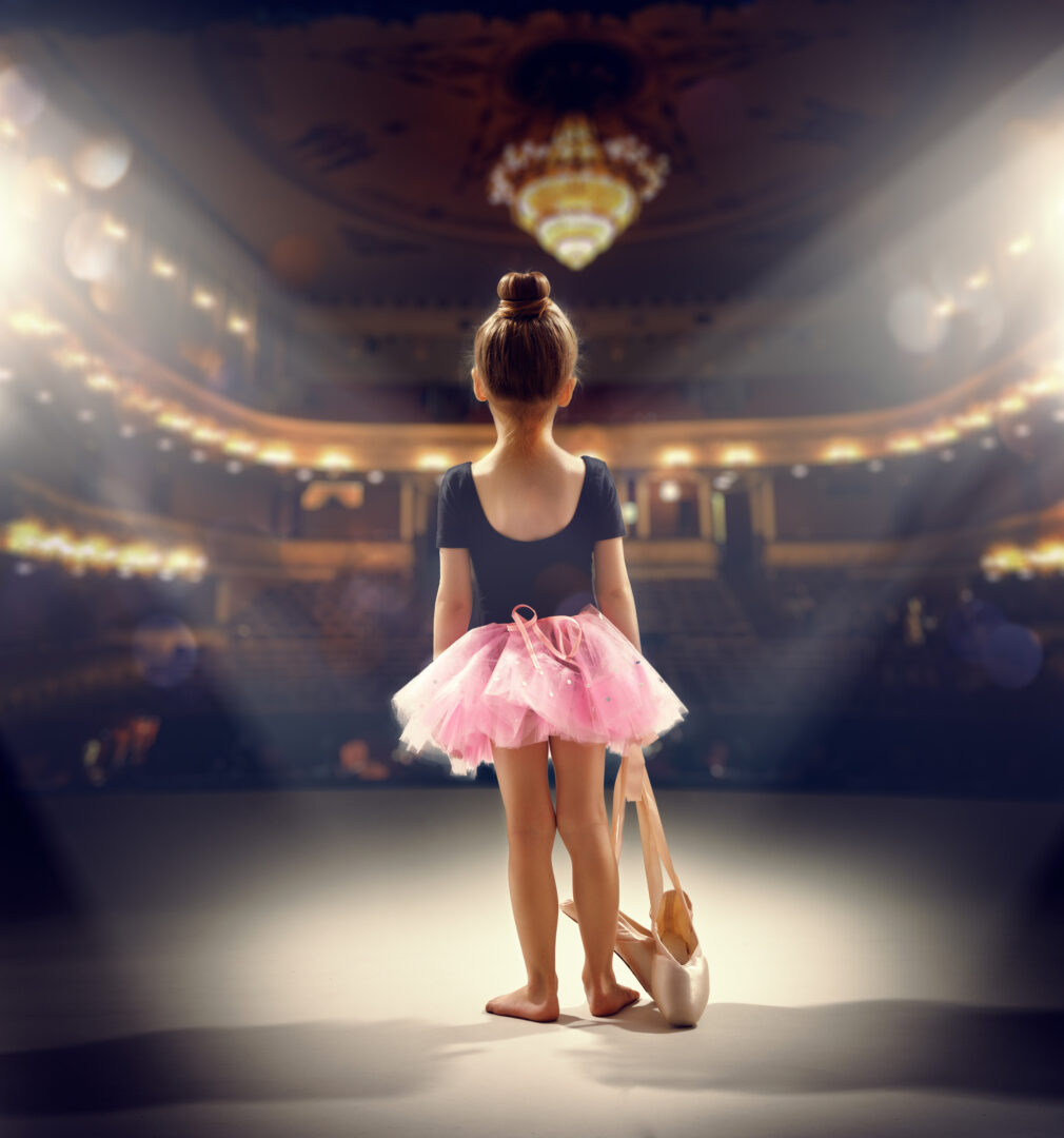 little girl on stage as ballerina holding point shoes
