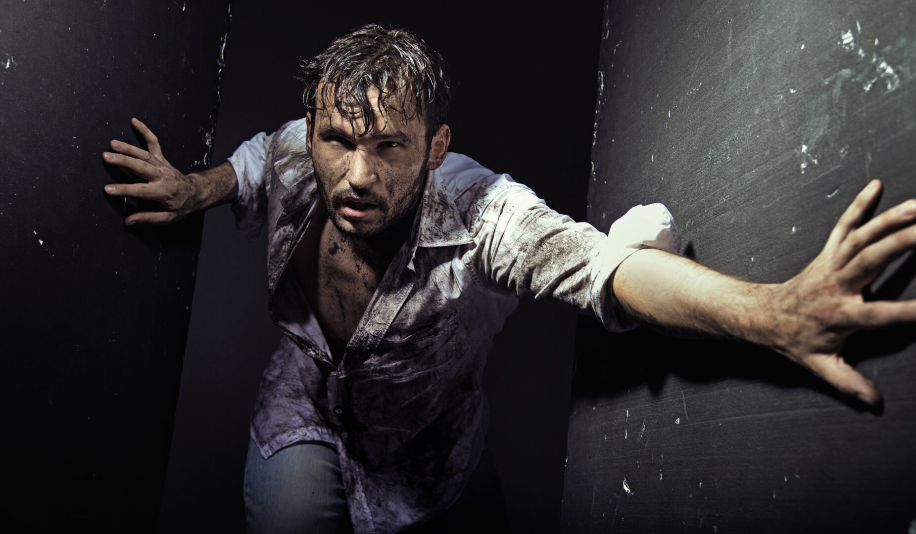 man wearing dirty clothes pushing against wall