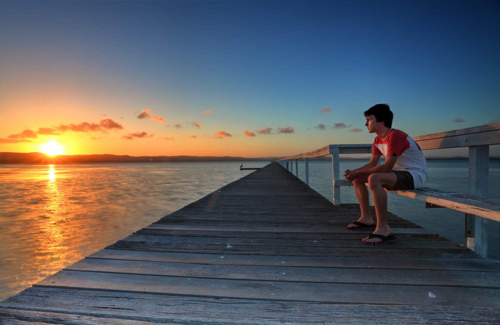 male sitting on pier at sunset over water